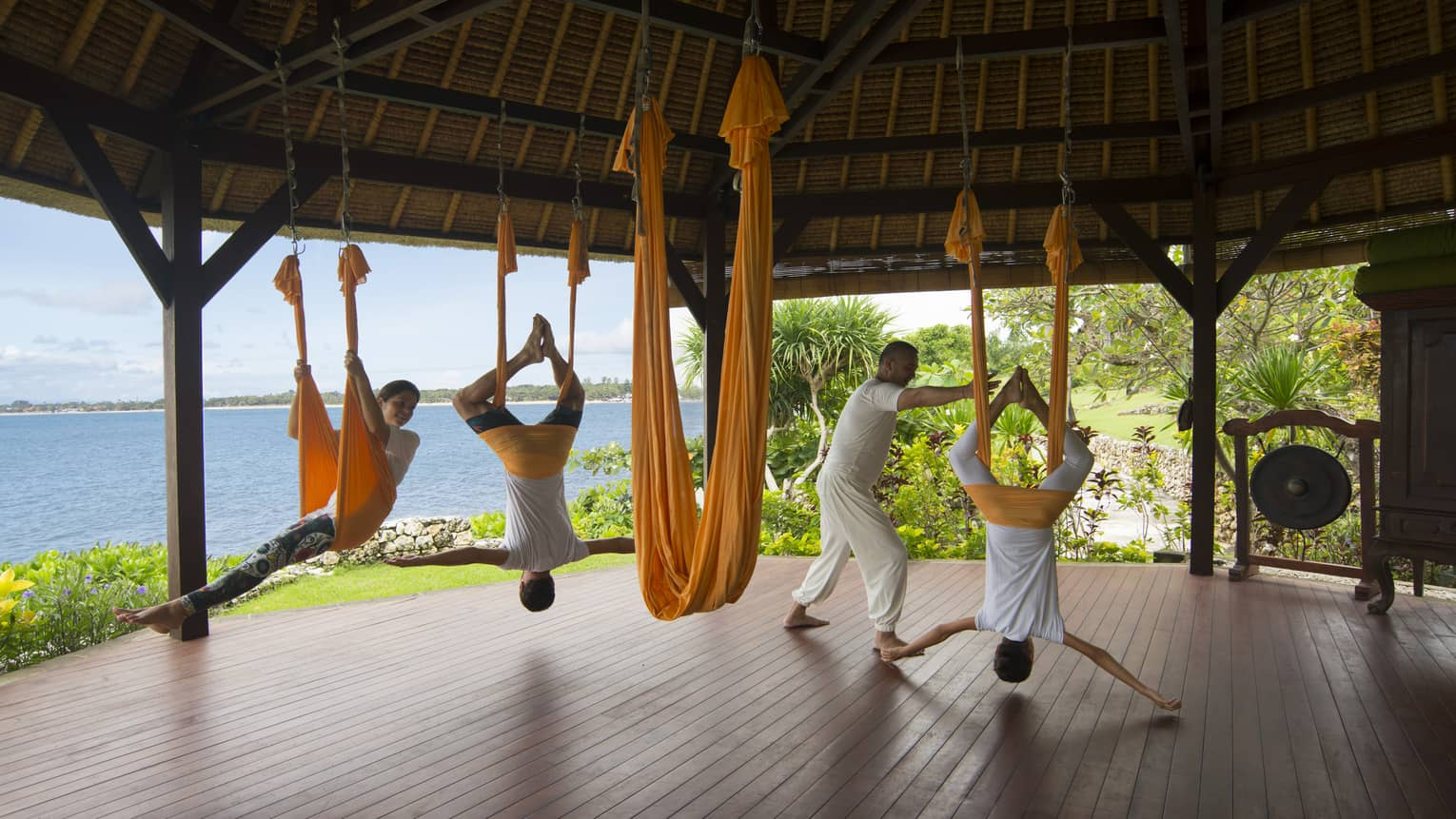 Guests hang from the ceiling as they are guided through rope yoga in an outdoor pavilion