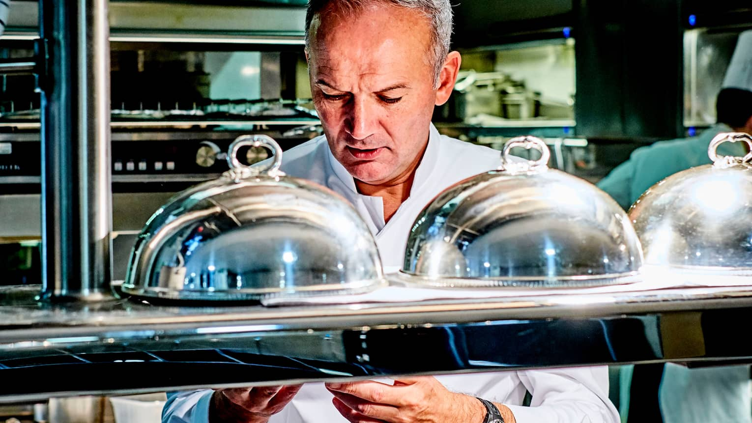 Le Cinq Chef Christian Le Squer behind kitchen line with metal cloche plate covers