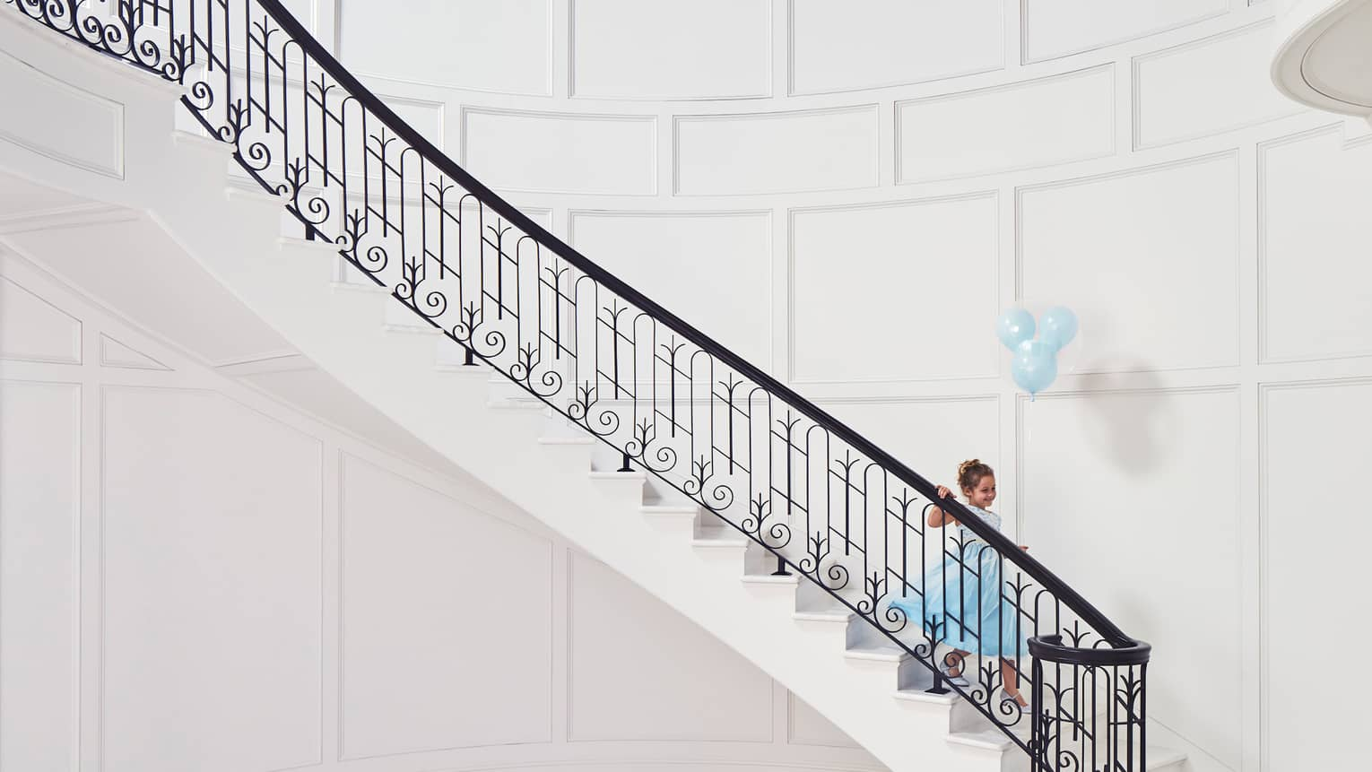 Child wearing blue gown with blue balloons walks down elegant white staircase with black iron railing