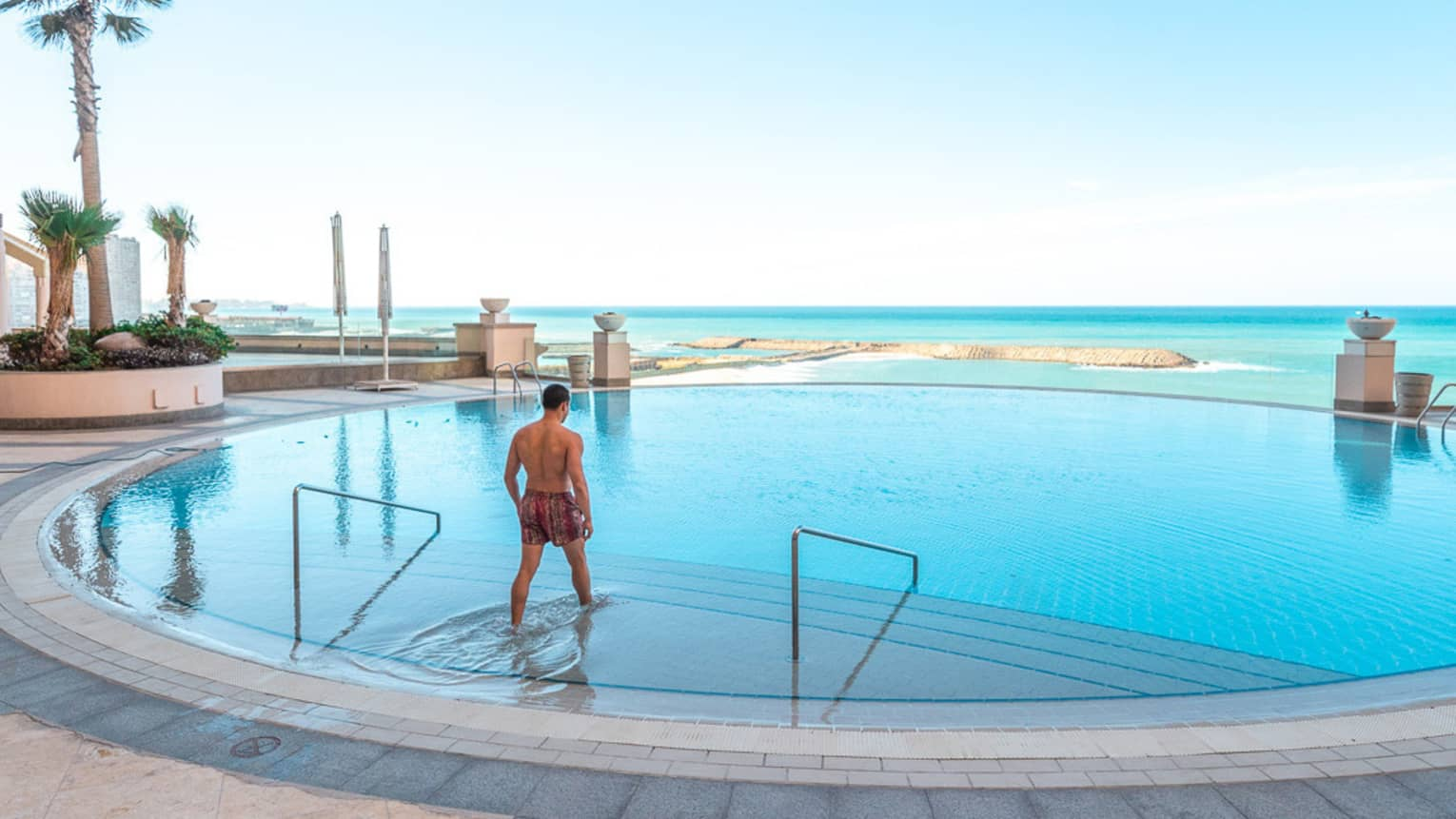 A man walking into the pool at four seasons hotel alexandria