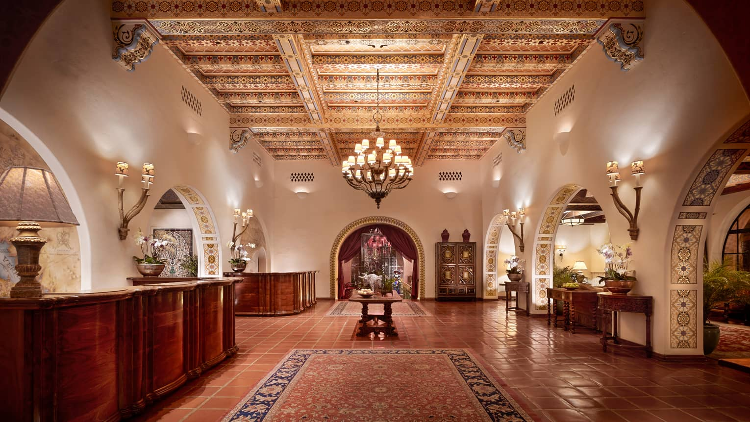 Colourful Spanish tiles covering ceiling, beams above chandelier, area rug, hotel lobby