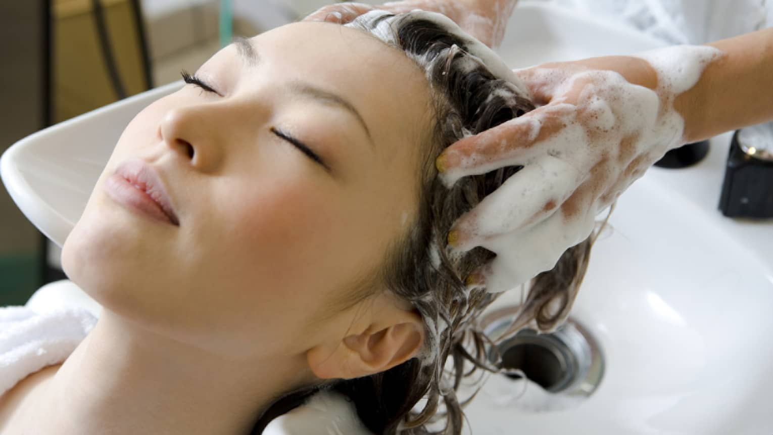 Woman closes eyes and leans back against sink as hands massage shampoo into her scalp