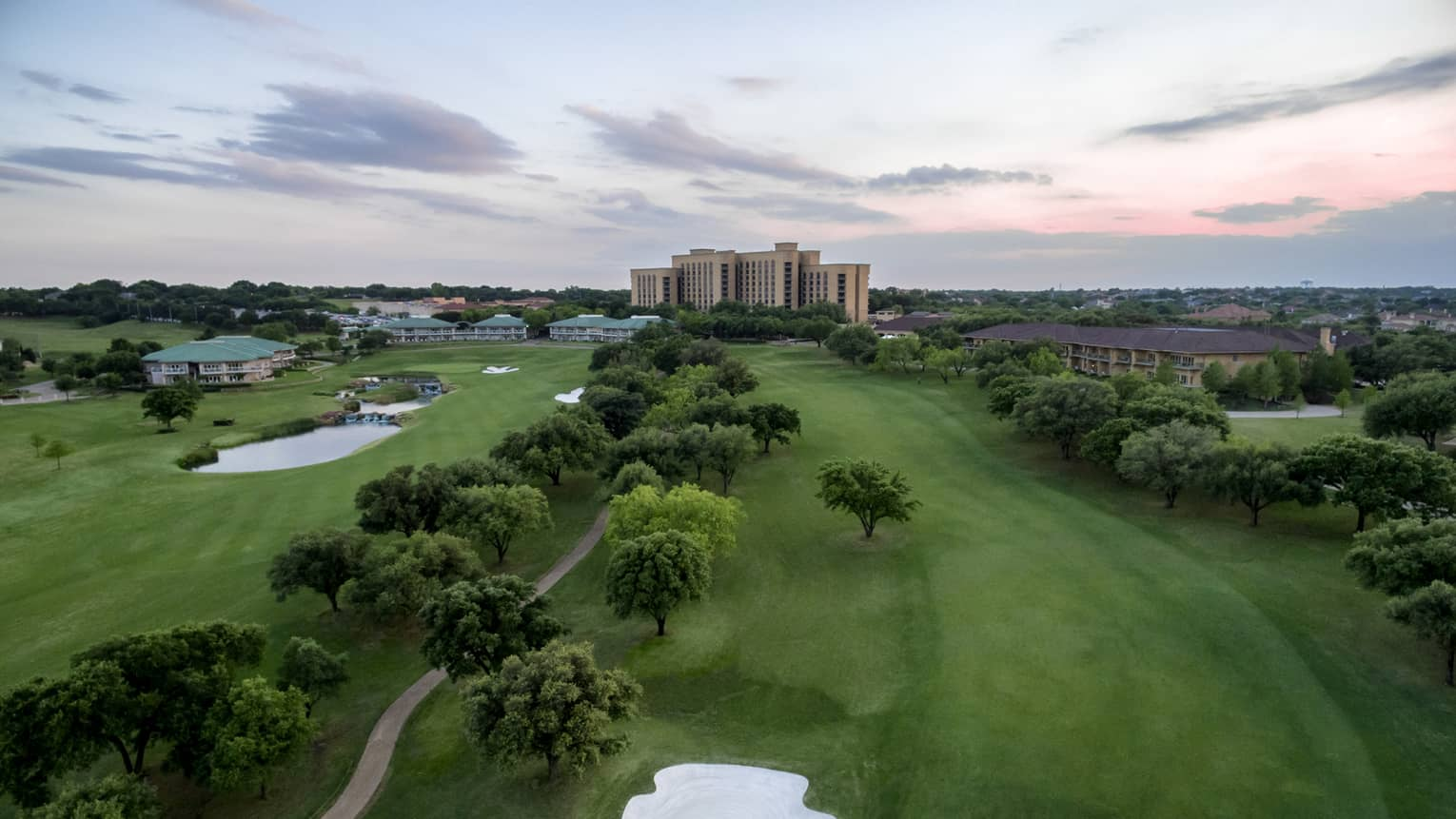 Aerial view of TPC Four Seasons Las Colinas golf course, small pond, trees and hotel highrise in distance