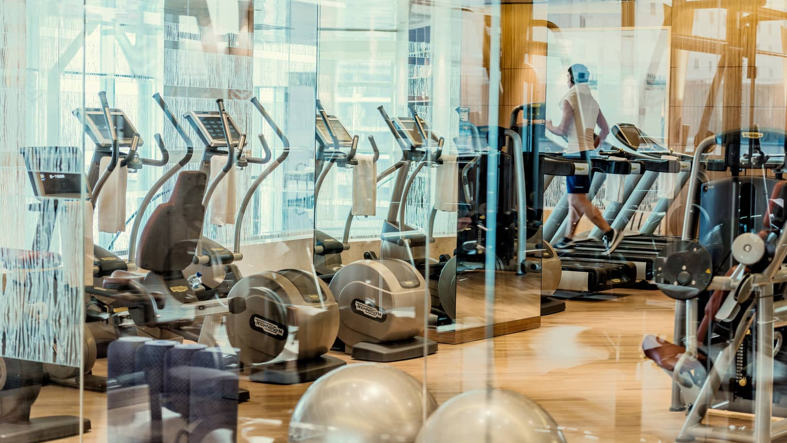 Rows of cardio machines, glass partitions in fitness centre Health Club