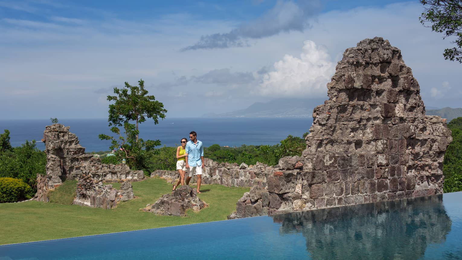 Couple walks through large stone ruins by pool