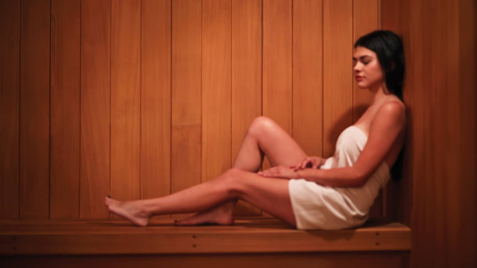 Woman in white towel with eyes closed rests back against wood wall, bench in sauna