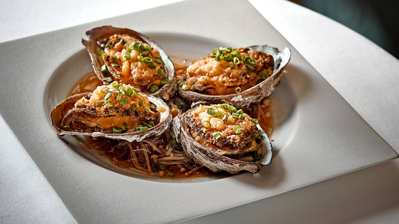 Four oyster shells with Steamed Live Abalone in bowl with sauce