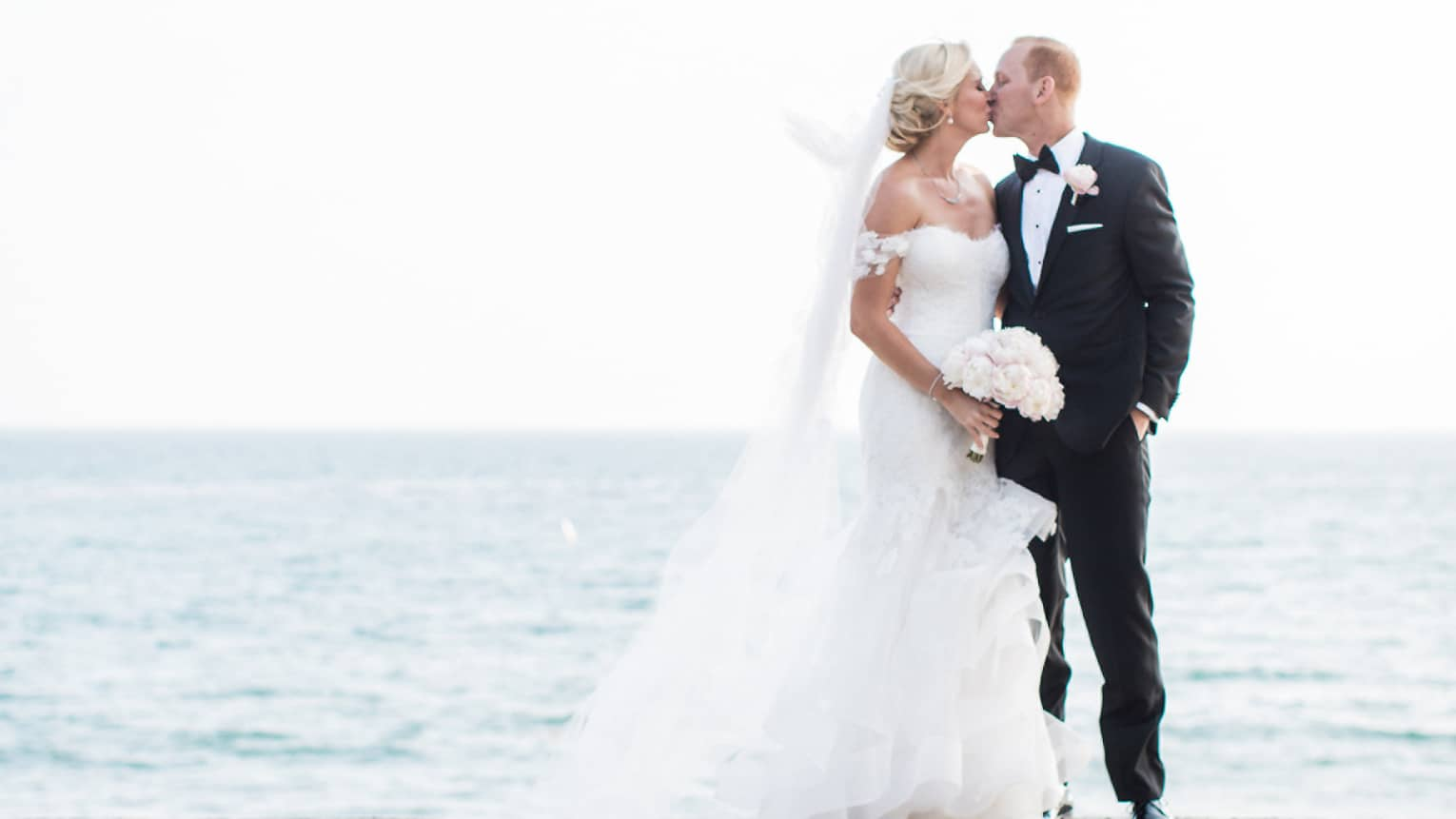 Bride and groom kiss in front of ocean