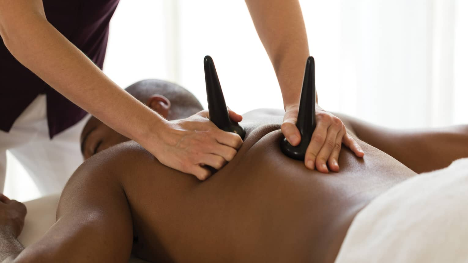 Masseuse pressed sculpted basalt stones on man's bare shoulders during massage