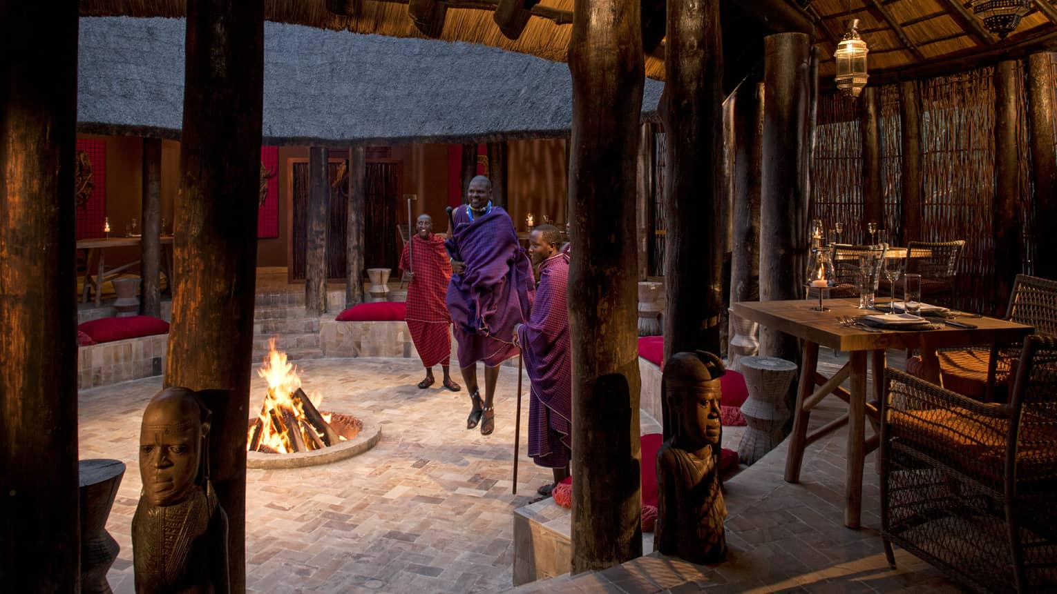 Maasai perform around a fireplace under a thatched hut with rustic tables and chairs at Boma Grill