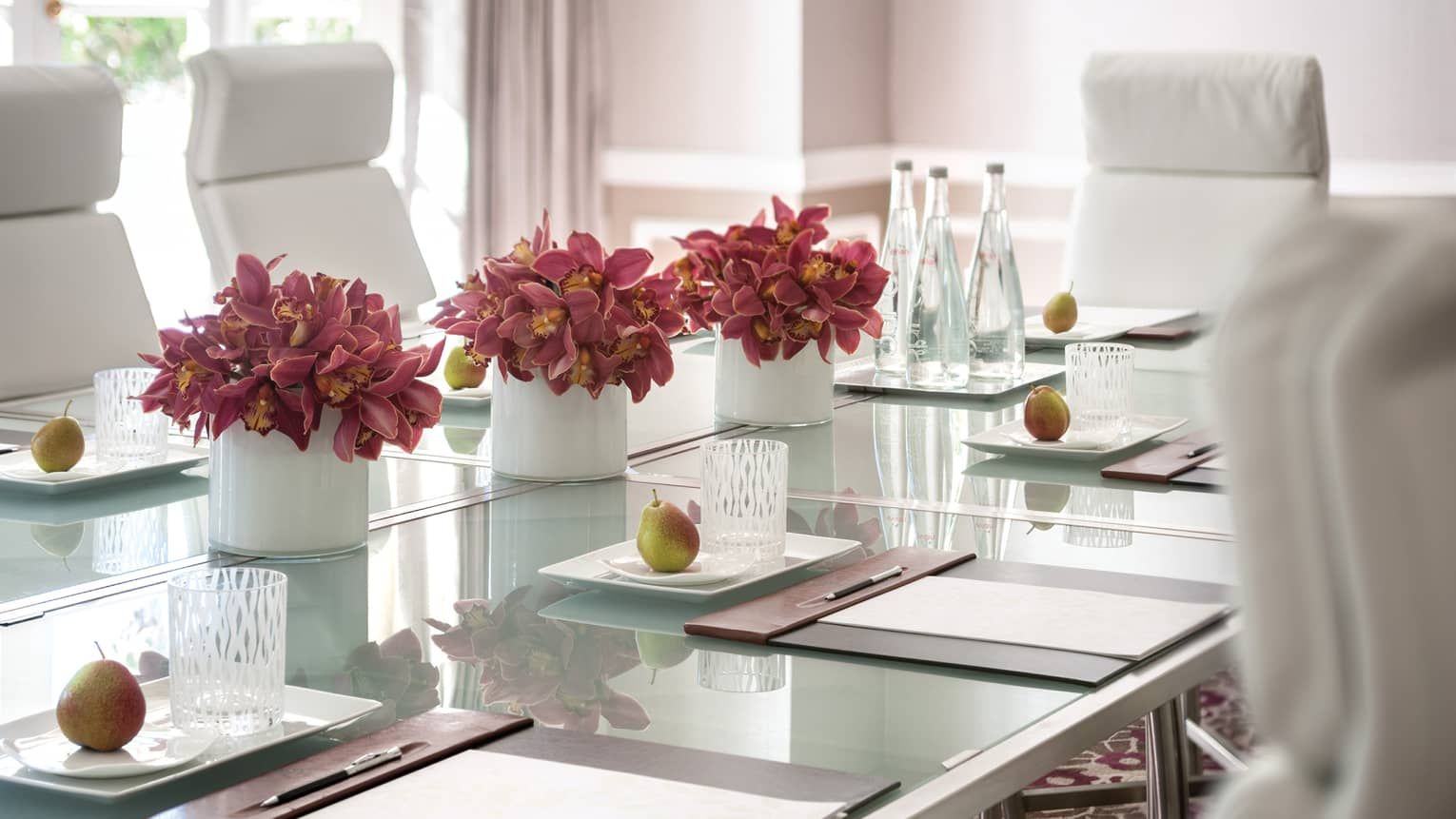 White chairs around frosted table with flowers, bottles of water, pears, glass and stationery