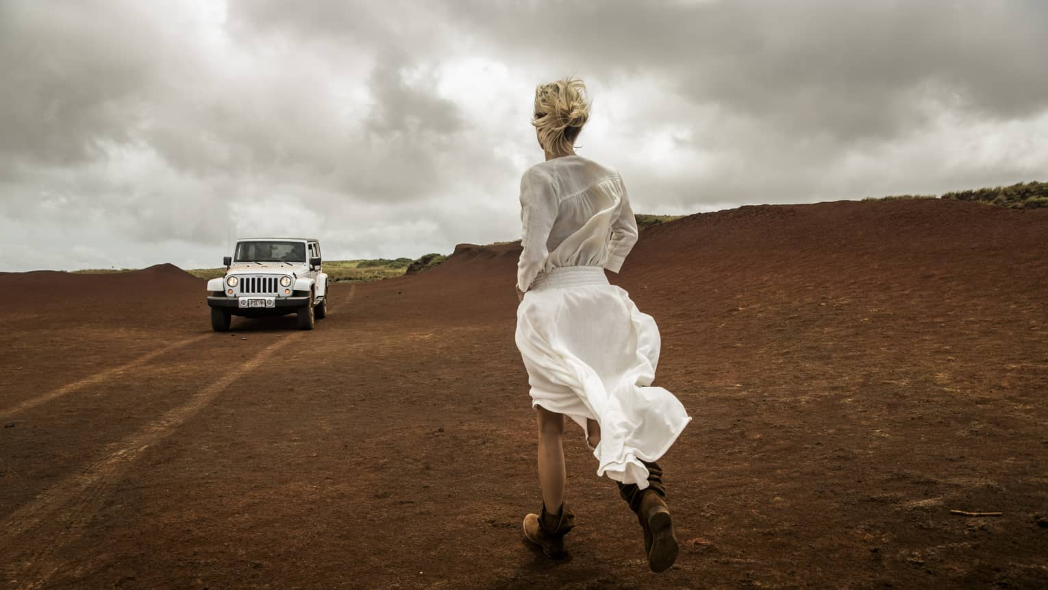 A white jeep approaches a woman on a windy day