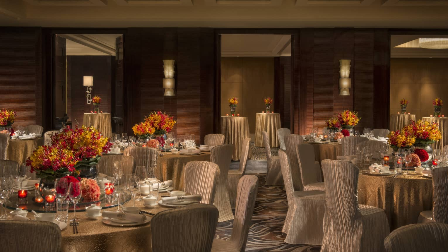 Dimly-lit ballroom with silk covered chairs around reception tables with orange flowers, candles
