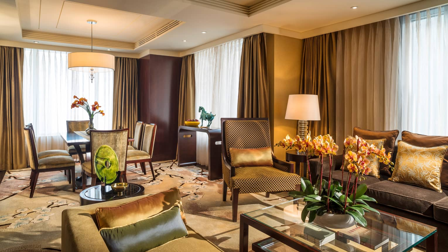 Chairman Suite living room with gold and green sofas and accent pillows, carpet, dining table, curtains on corner windows
