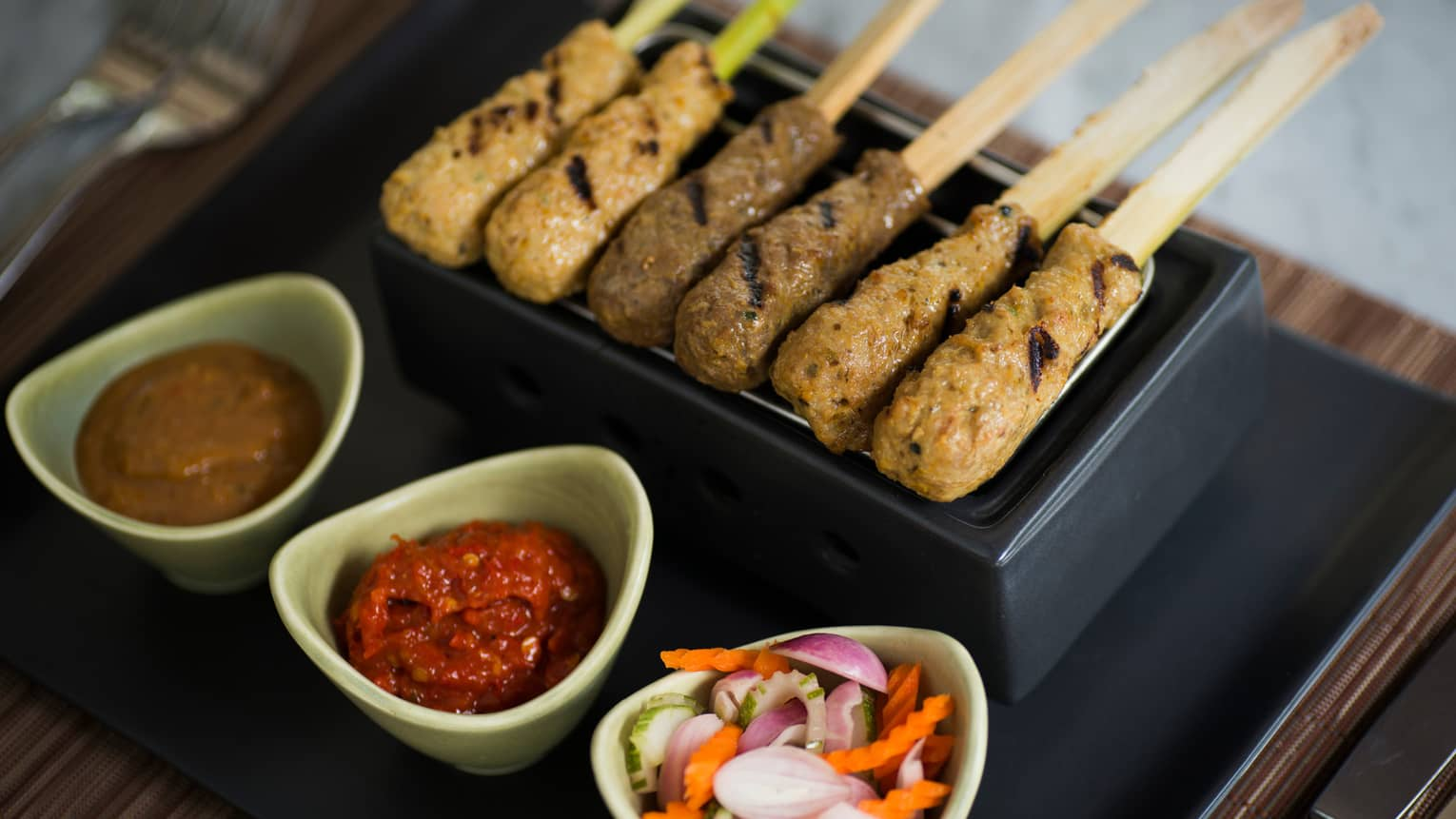 Satay Lilit mixed Balinese skewers lined up in black tray, three white bowls with satay sauce, sliced vegetables