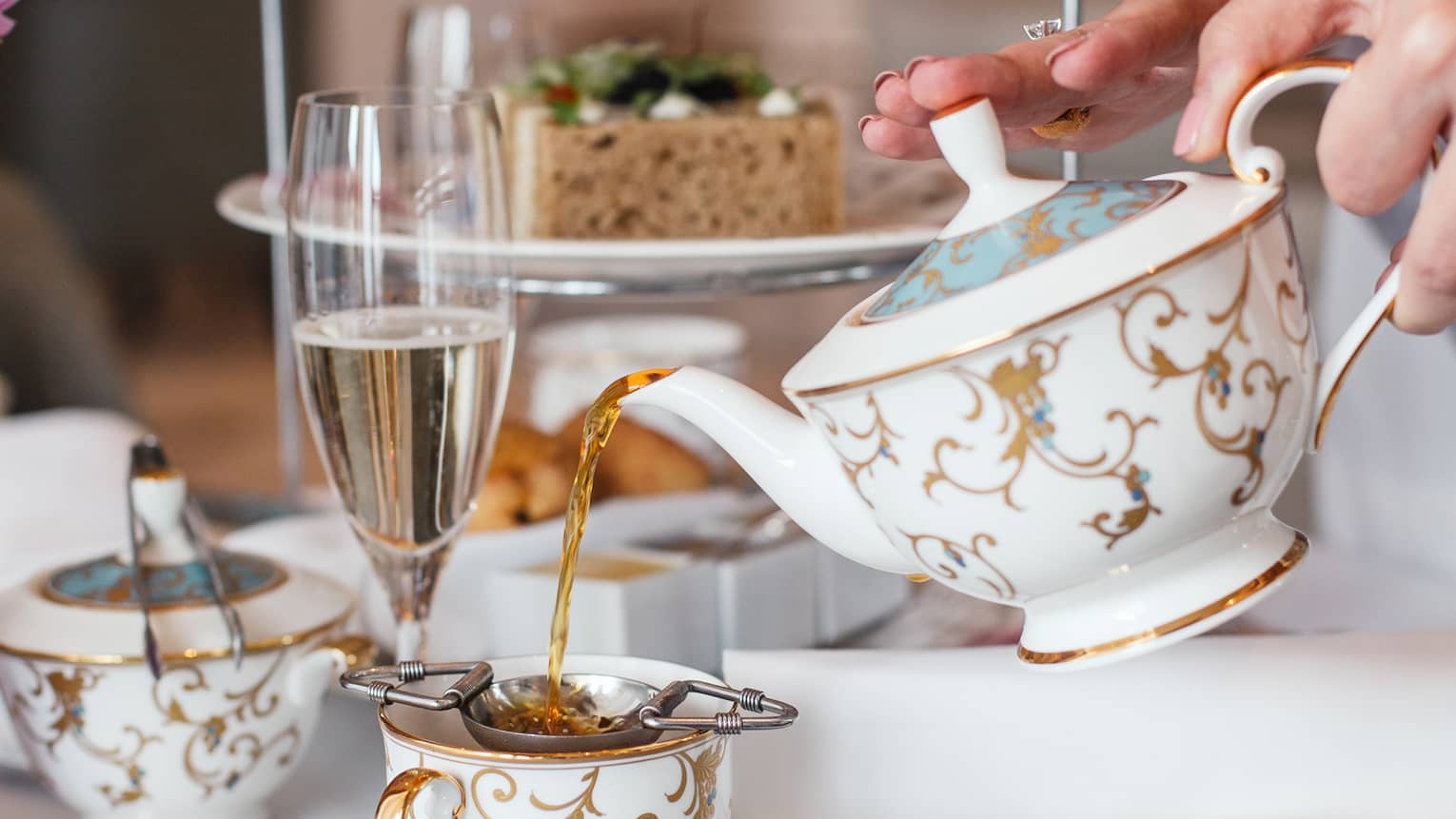 Hotel staff pours gold and white teapot by dessert tray at afternoon tea