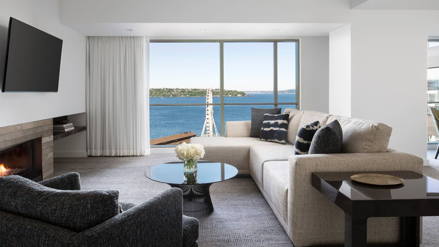 The living room's floor-to-ceiling windows look at to Elliot Bay in the Deluxe Elliot Bay Suite