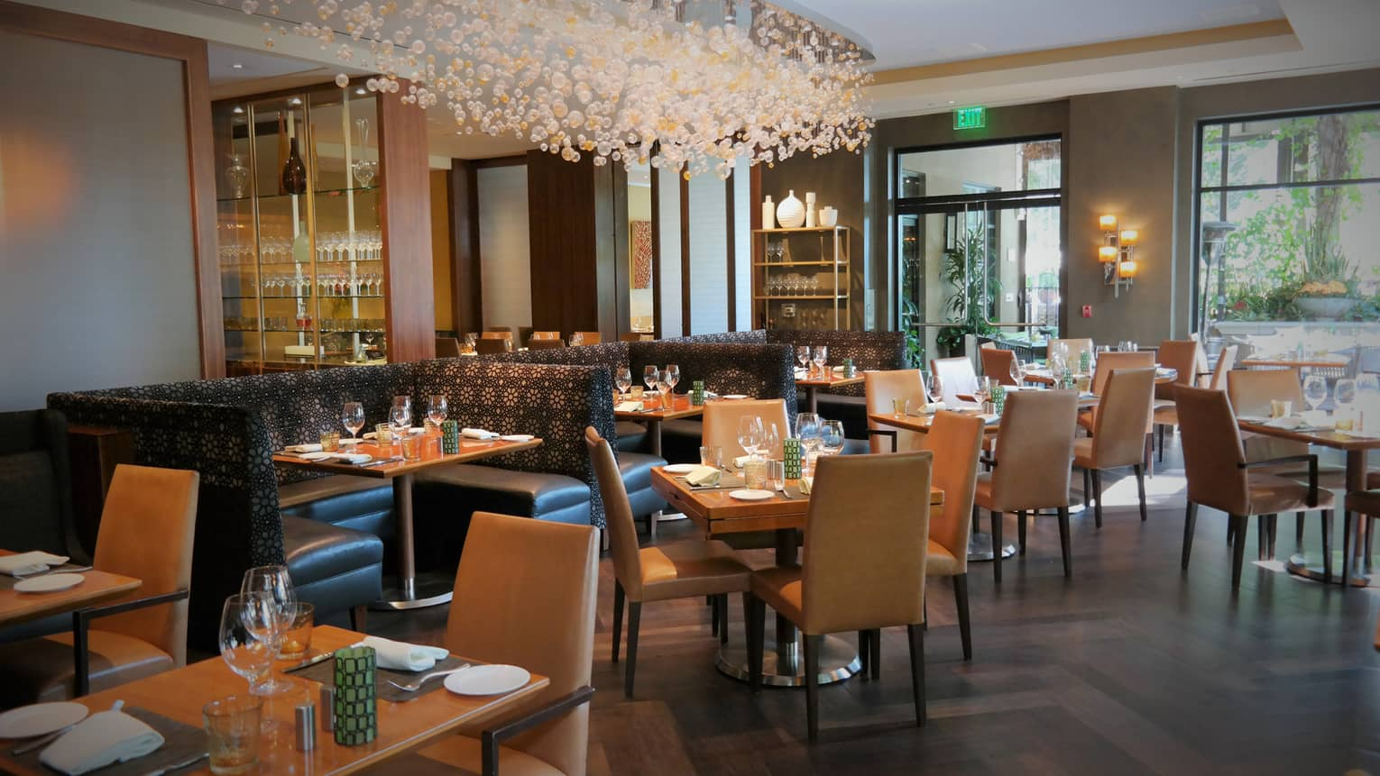 Culina Restaurant dining tables, chairs, booths under modern chandelier