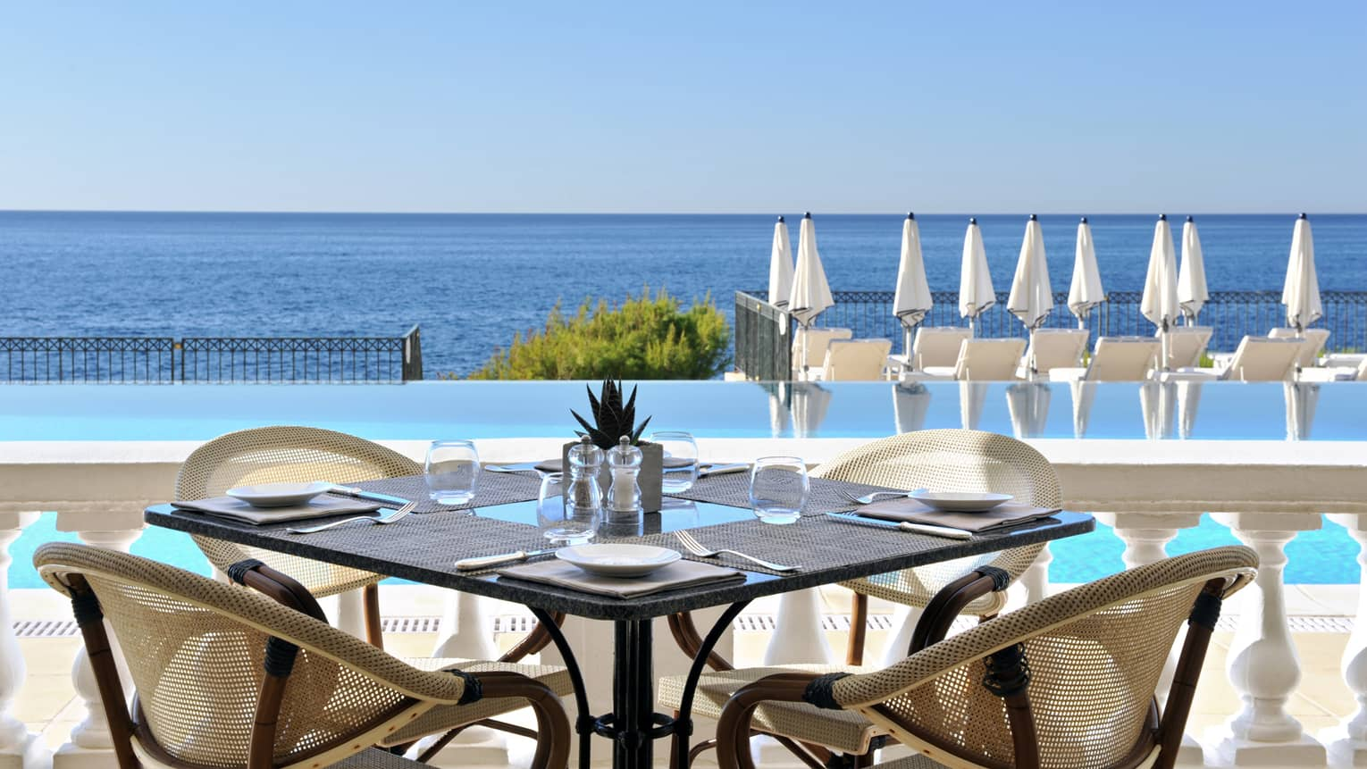 Club Dauphin patio table, chairs by outdoor swimming pool, blue sea