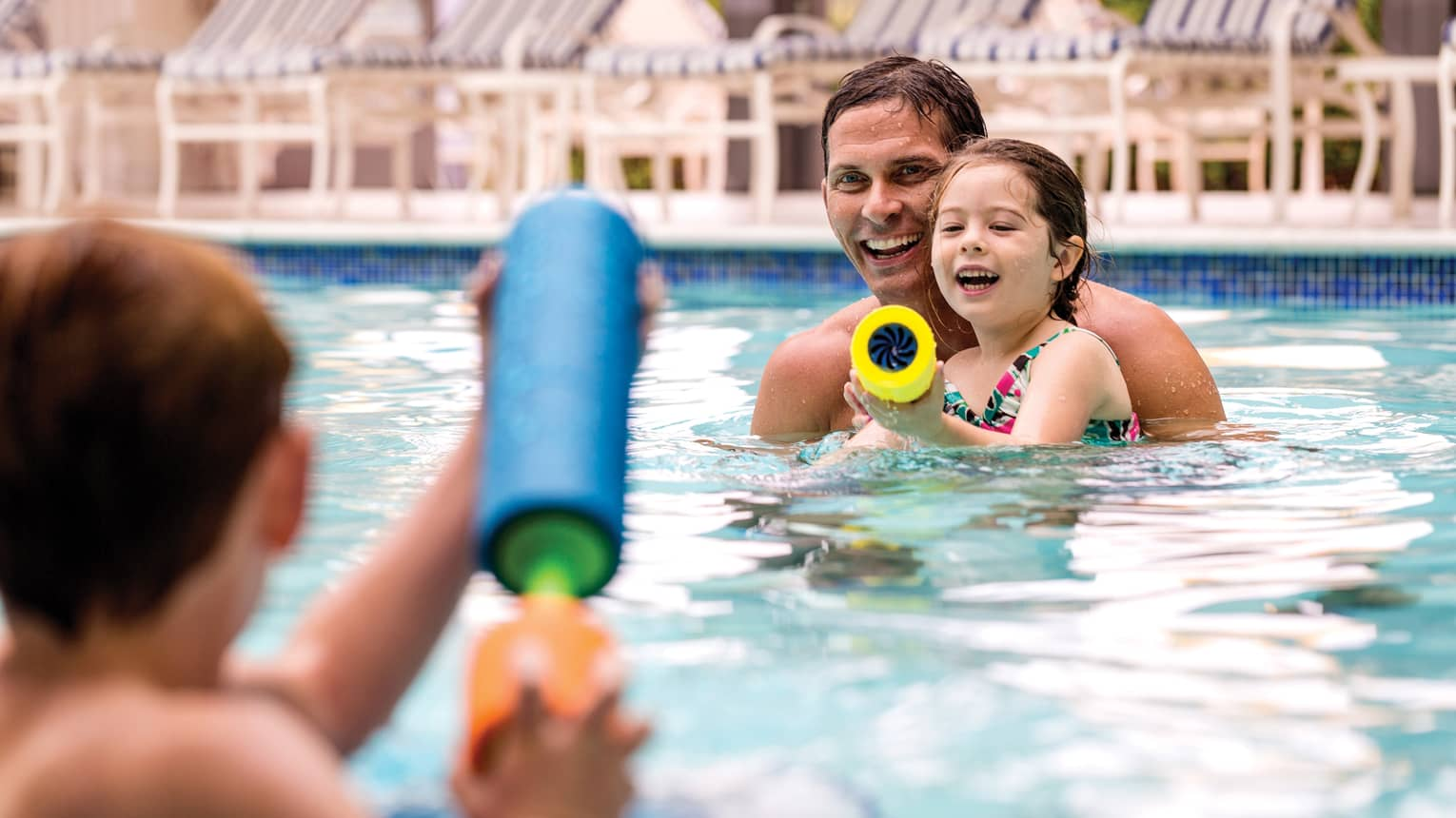 Smiling family swimming in outdoor pool squirt water guns at each other
