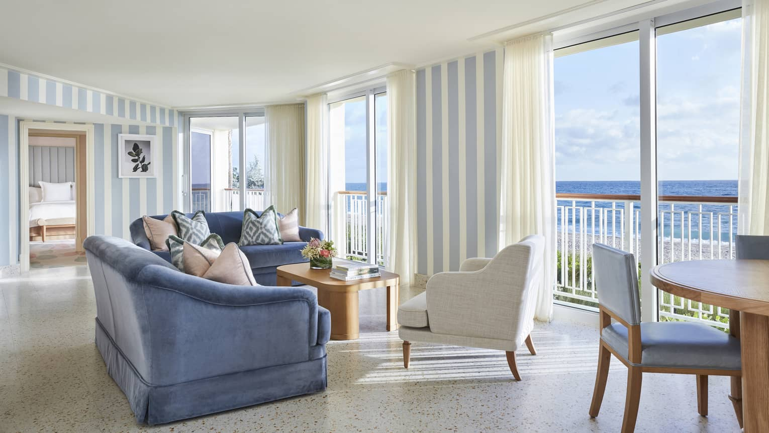Living area in a suite, with blue sofas, a white armchair and floor-to-ceiling views of the ocean