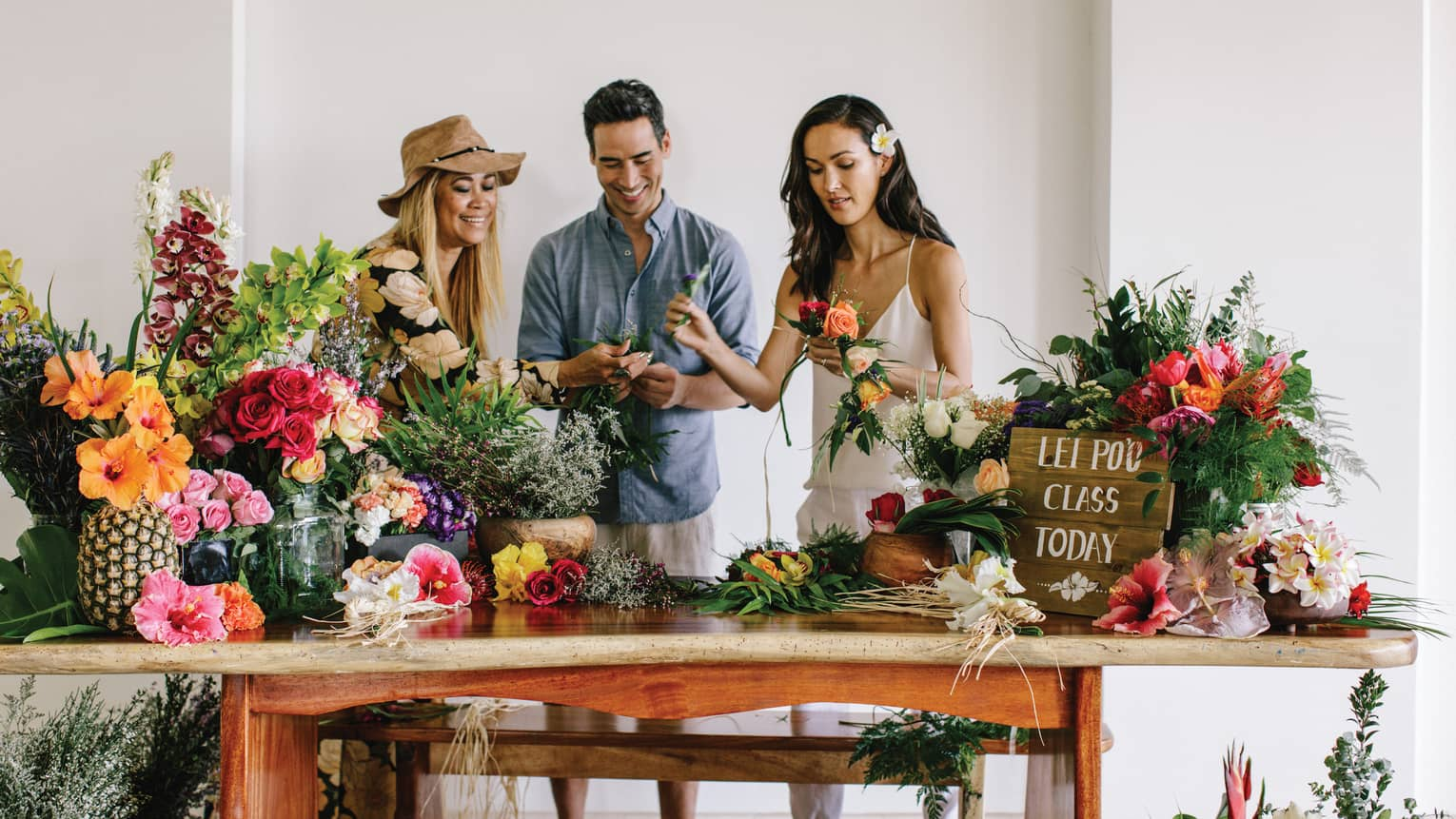 Two women and man make lei necklaces during class at wood table covered with fresh flowers