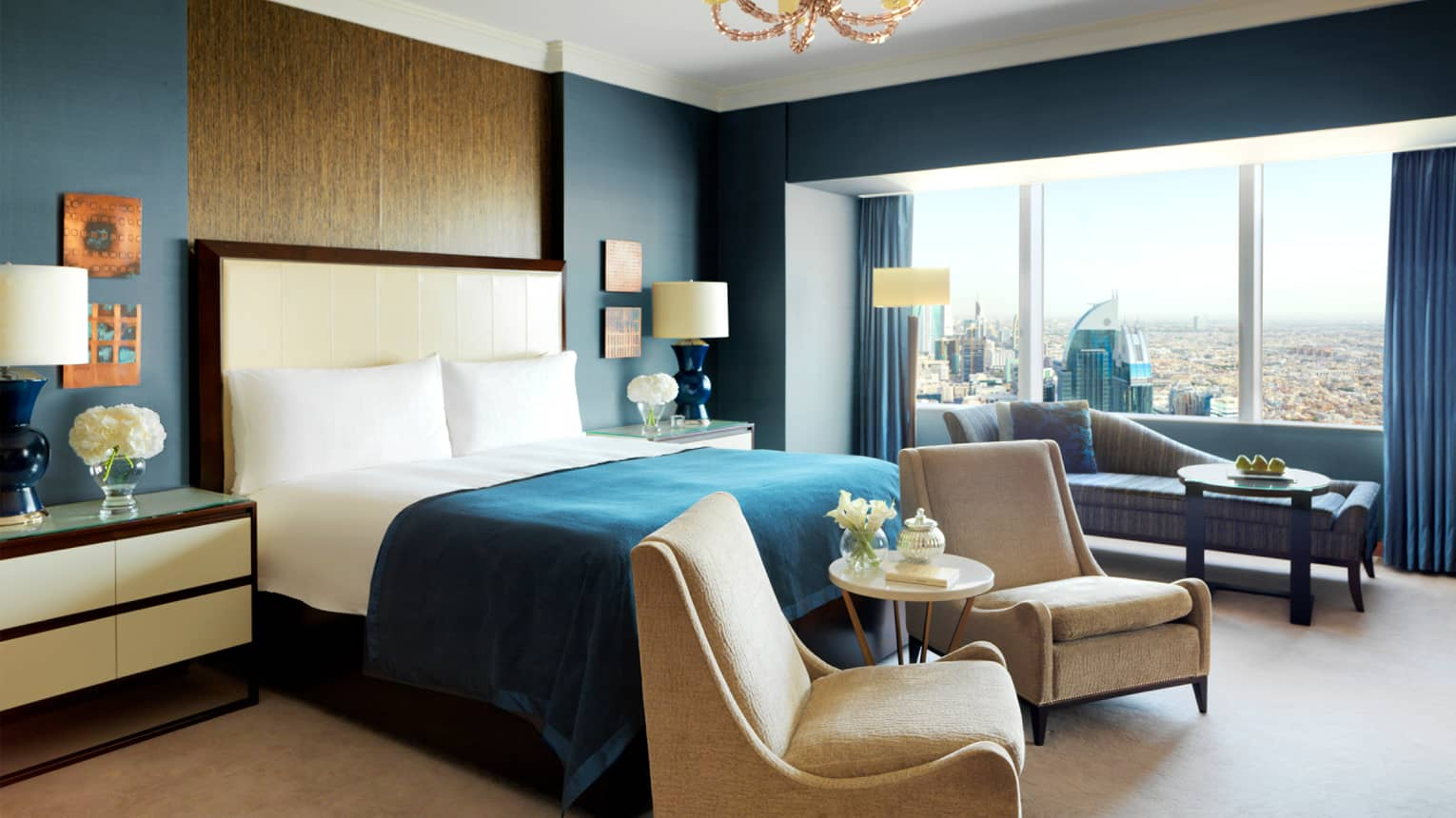 Presidential Suite with bright blue and beige decor, tall wood panel behind headboard, two armchairs, chaise