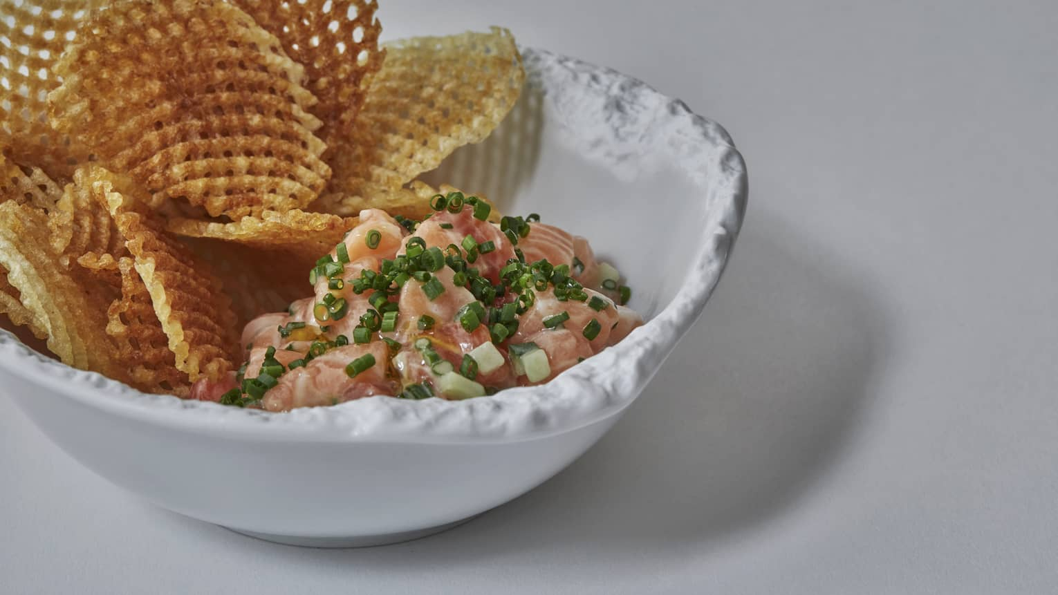 A waffle fry and salmon dish in a white porcelain bowl