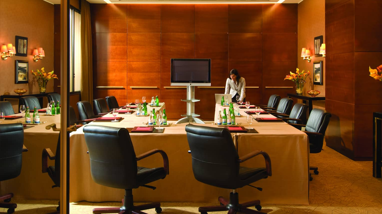 Woman stands in front of U-shaped meeting table set with folders, bottles of water, lined with black office chairs