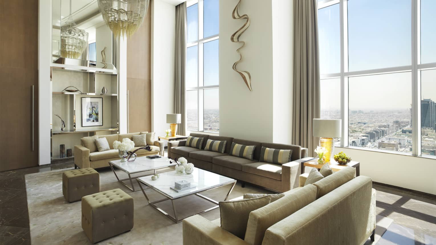 Kingdom Suite with tall ceilings and windows, three sofas, two chairs and coffee tables, large chandelier and wall sculpture
