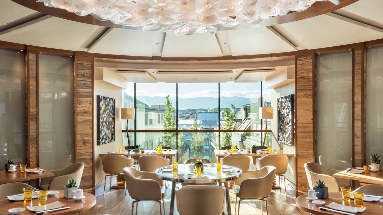 Sunny rotunda dining room with cream-coloured chairs, round wood tables, floor-to-ceiling window