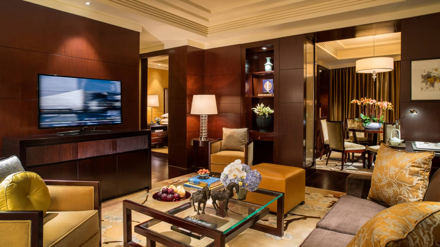 Beijing Suite living room with sofa, gold pillows and armchair, large TV, wood panel walls