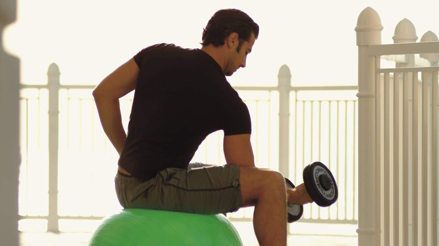 Back view of man in workout gear with hand weight, seated on exercise ball
