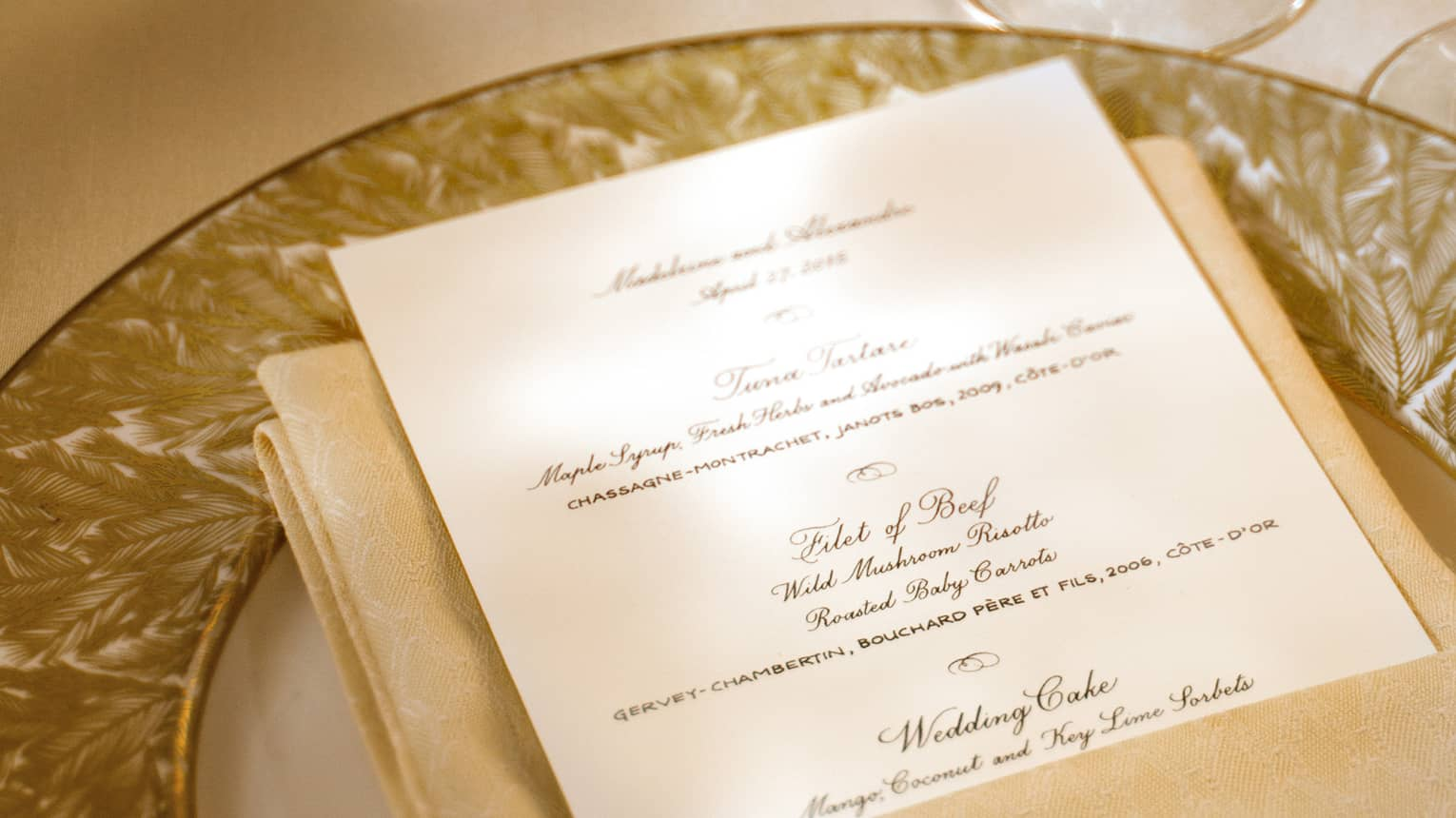 Close-up of wedding menu on gold plate near wine glasses, candles