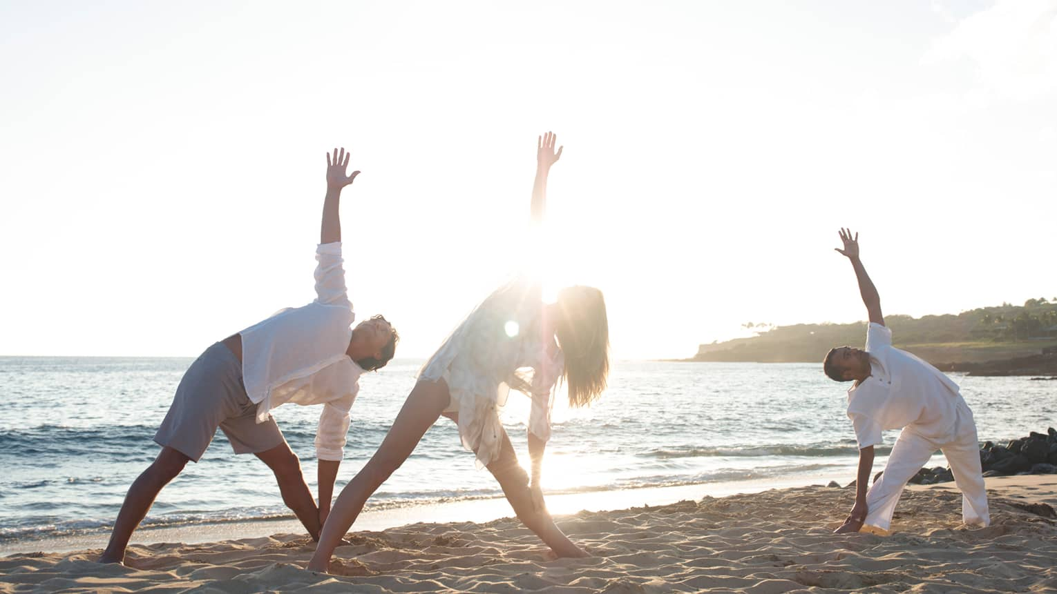 Three people stretch in yoga pose on sand beach at sunrise