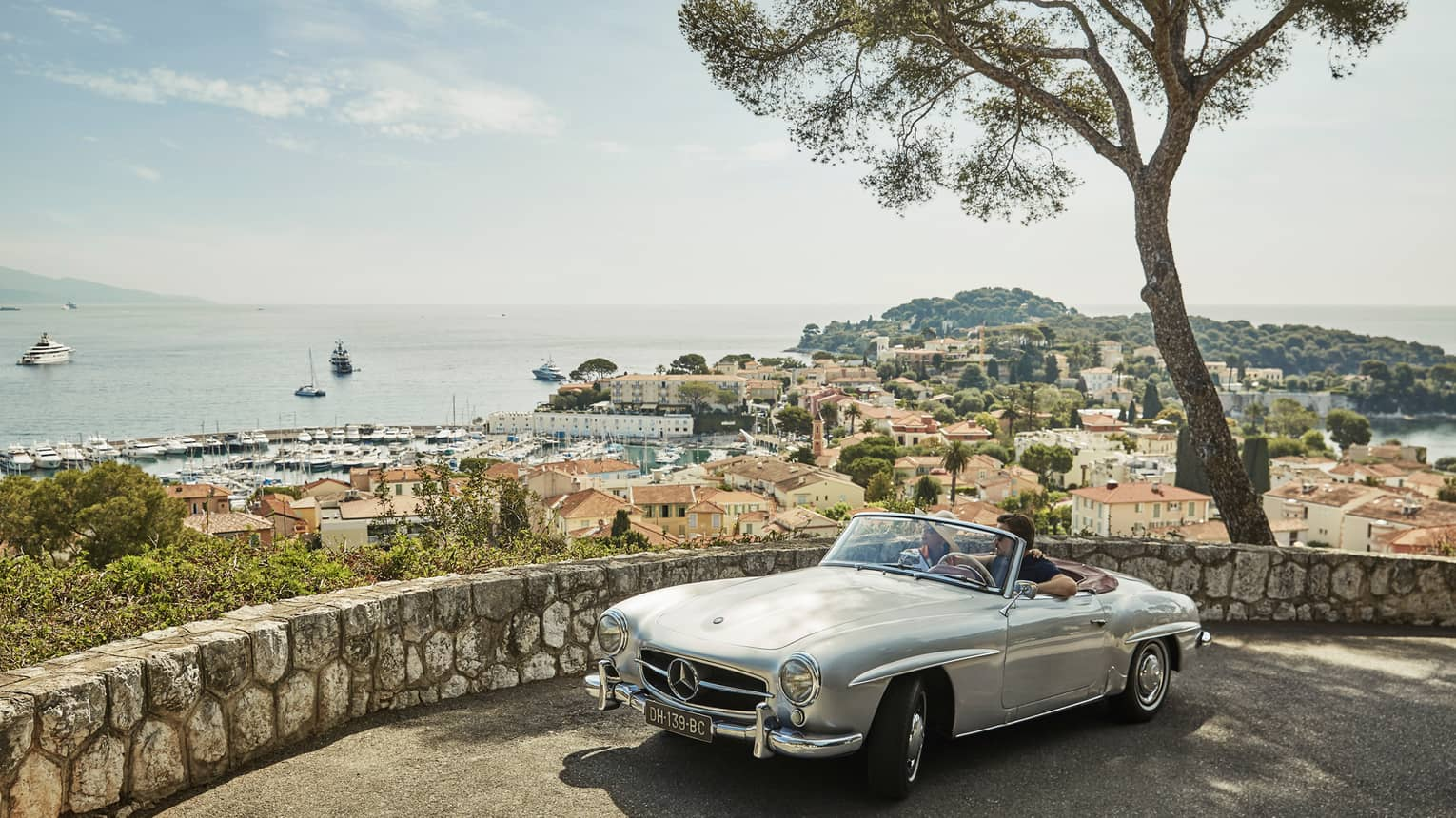 Couple in luxury vintage white car parked under tree by stone wall overlooking red roofs, water