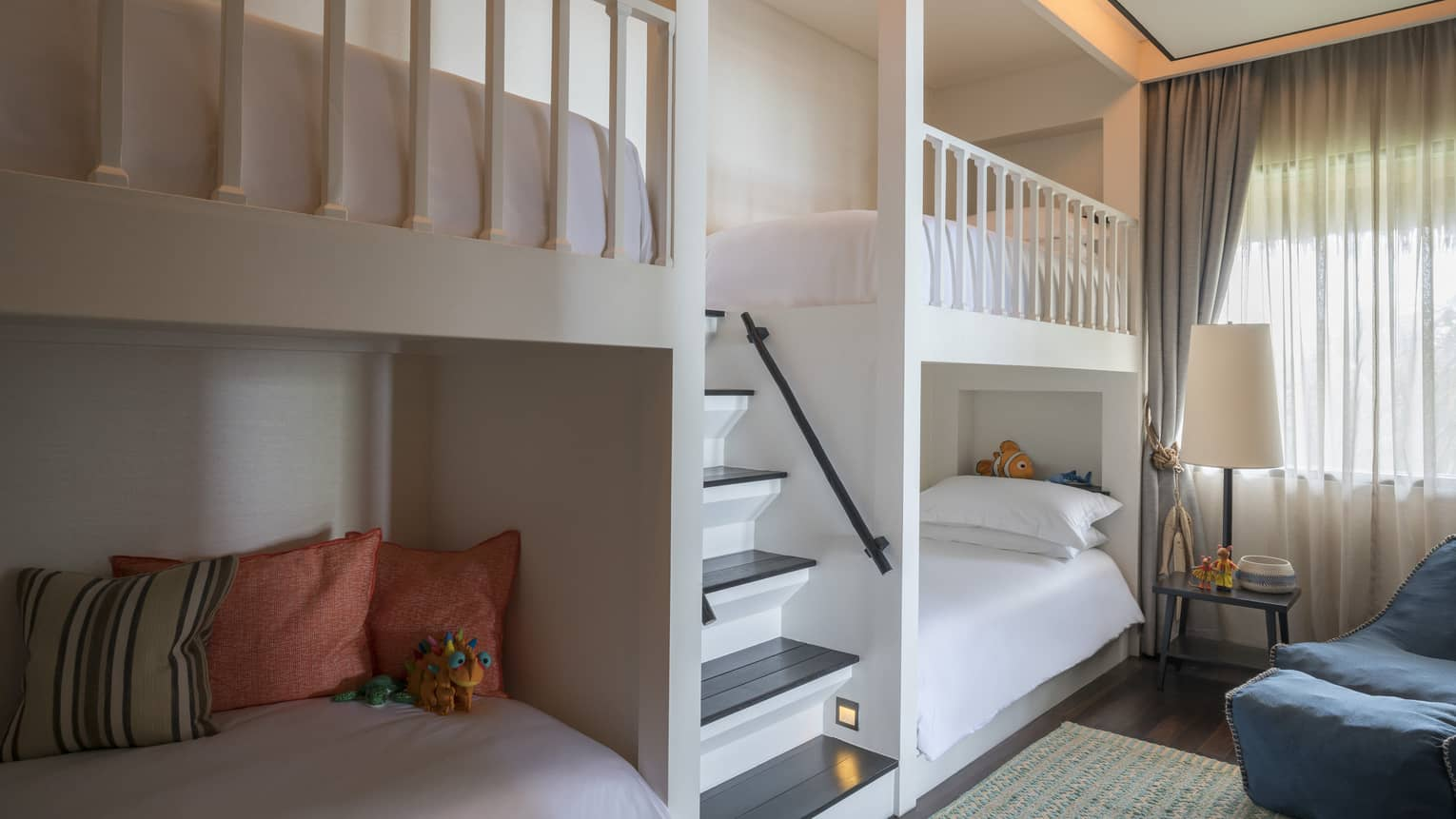 Bunk beds, pillows on either side of small staircase in children's room