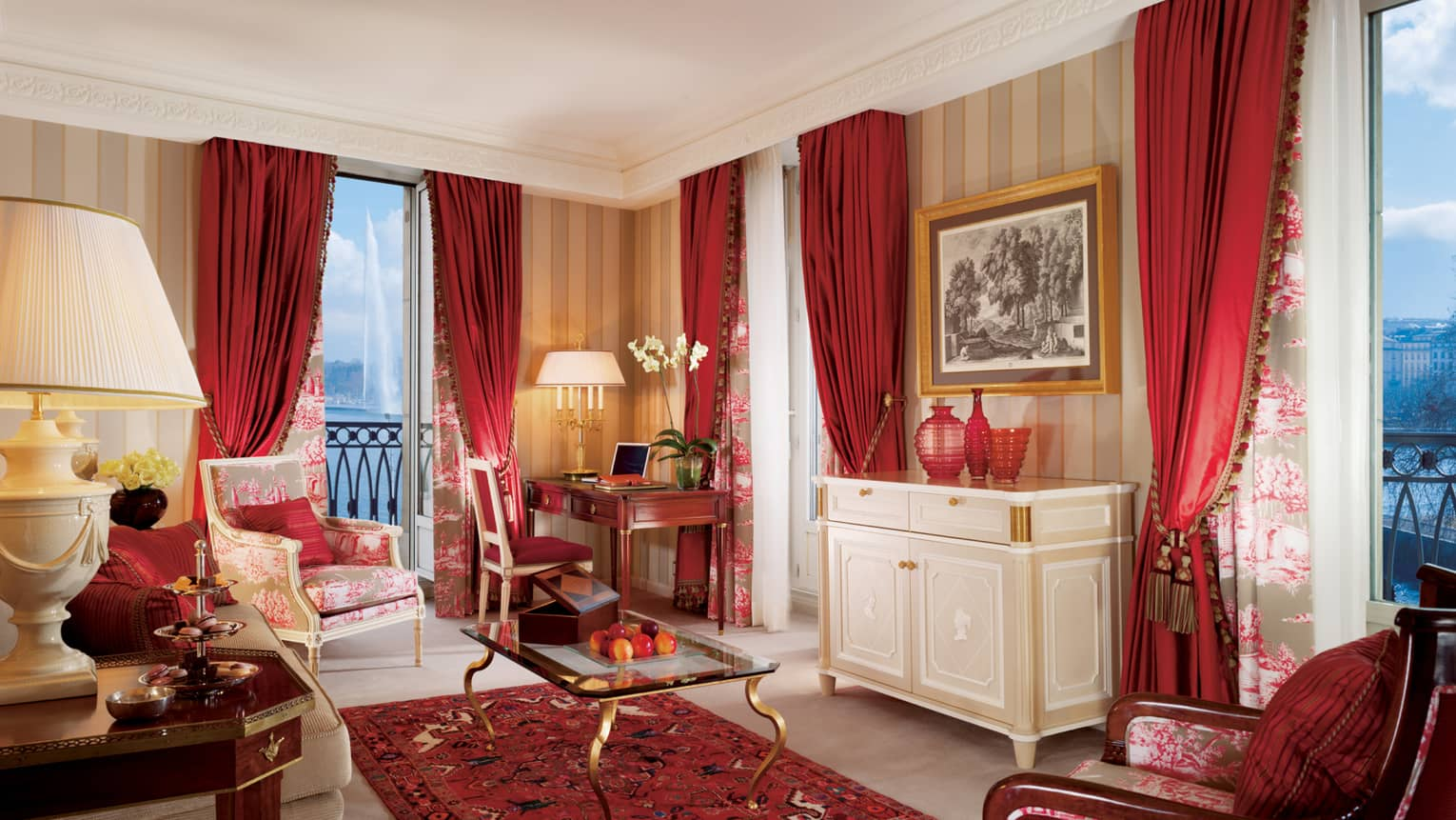 Suite Mont Blanc with dark red curtains, accent chair and rug, glass coffee table, French balcony at dusk