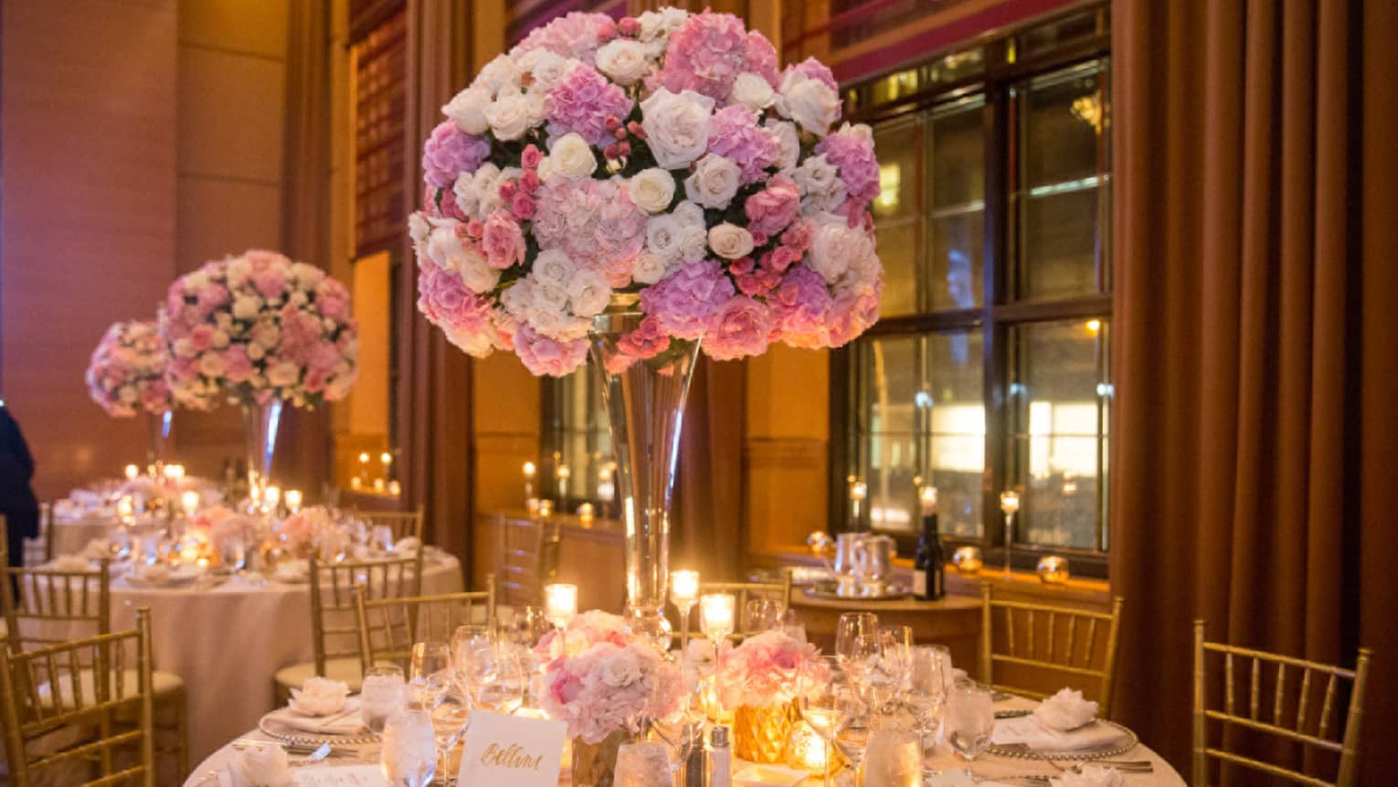 Wedding banquet dining tables with glowing candles, pink rose bouquets in tall vases