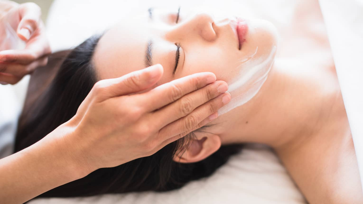 Close-up of spa attendant's hands rubbing white cream on woman's face as she lies on massage table