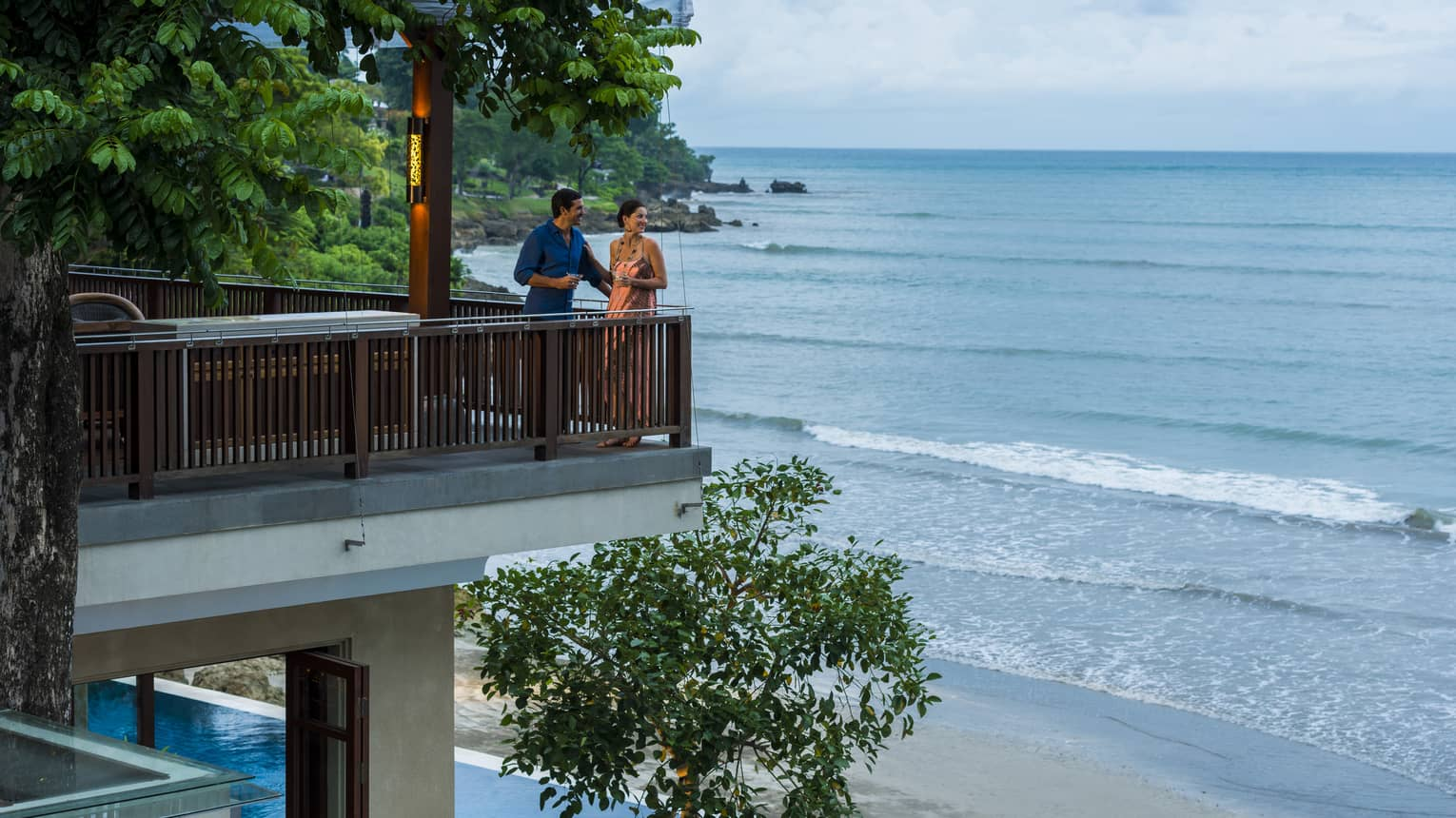 Man and woman stand at corner of balcony, look out at ocean