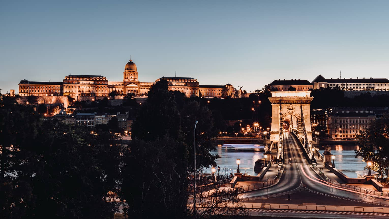 Széchenyi Chain Bridge over the Danube River, uplit Buda Castle at night