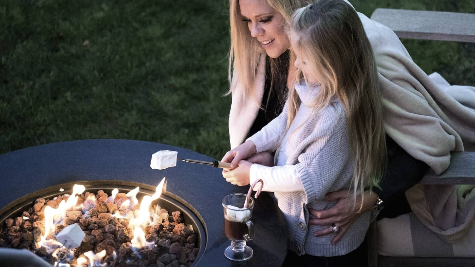 Woman puts her arms around girl roasting marshmallow over a fire pit