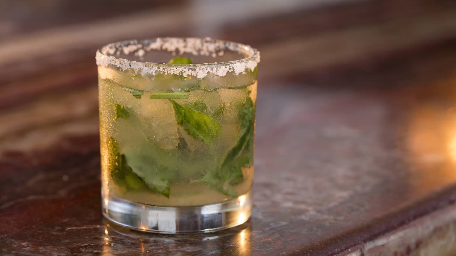 Cocktail with muddled mint leaves, salt rim around rock glass in bar
