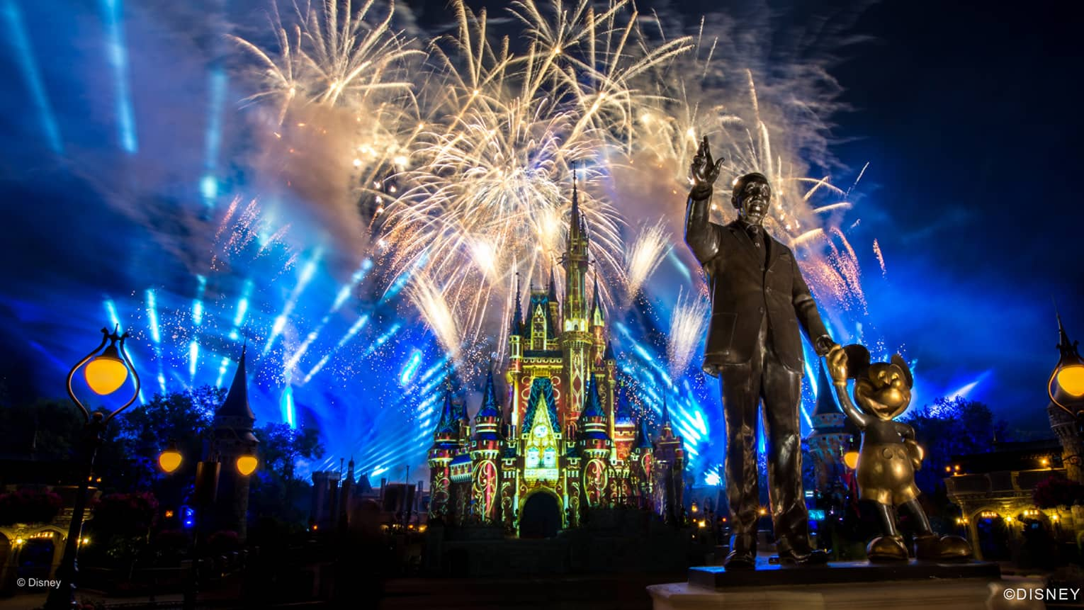 Fireworks and blue lights fill the night sky above the monument of Walt Disney at Disney world in orlando florida