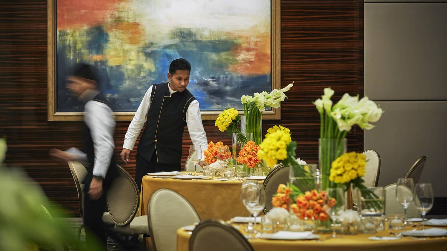 Server in black-and-white uniform sets round formal dining table with yellow linen, vases of fresh orange, yellow flowers