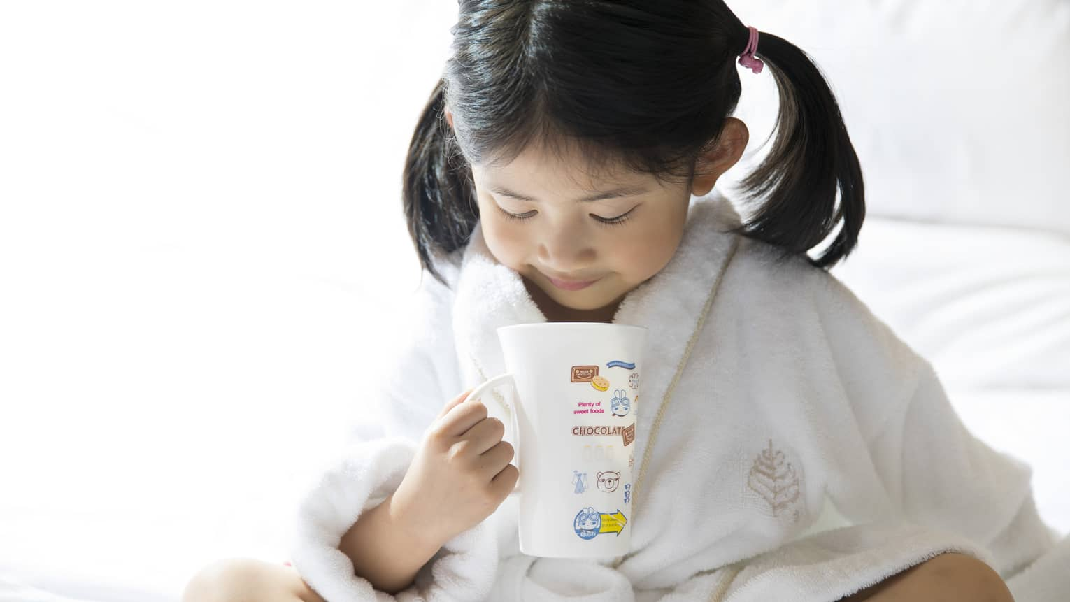 Young child in white bathrobe with hair in ponytails sits cross-legged on bed, holds mug of hot chocolate