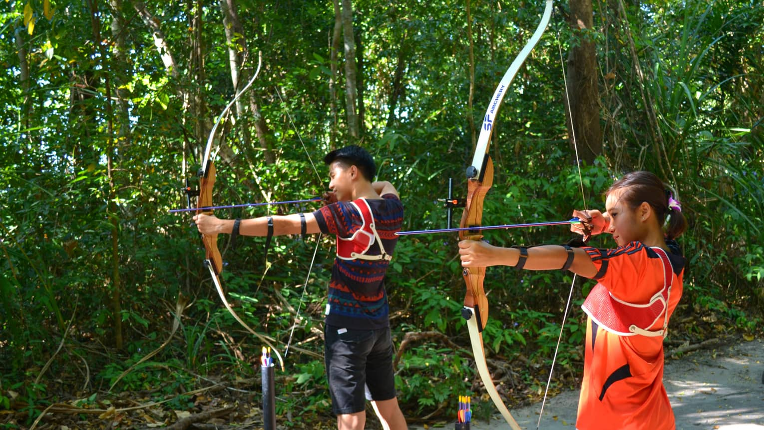 Man and woman stand with archery bow and arrows, prepare to shoot