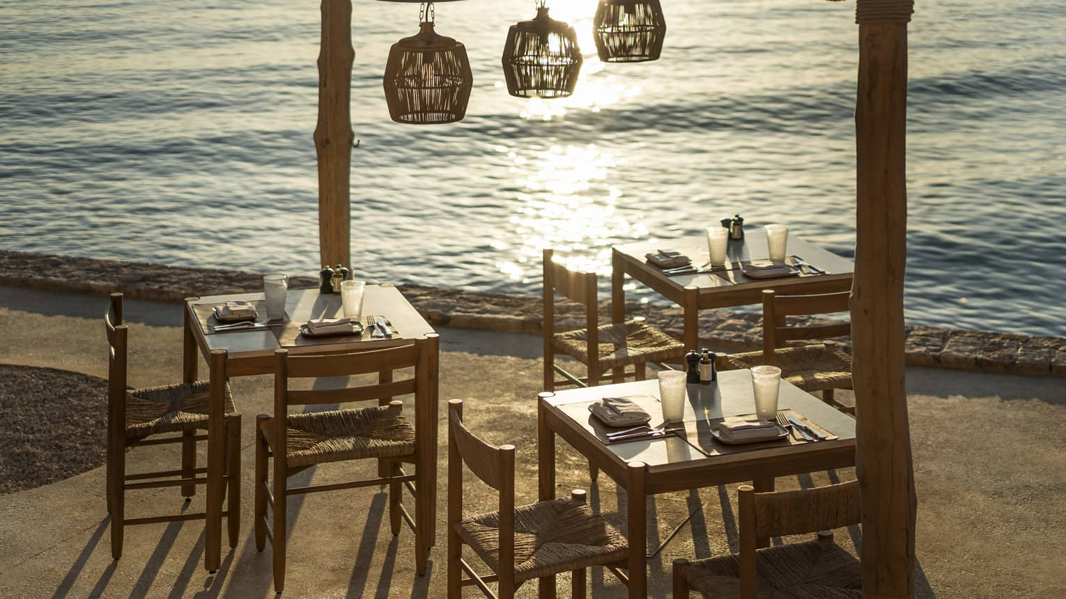 Outdoor taverna next to ocean with three wooden tables and chairs, three wooden lamps