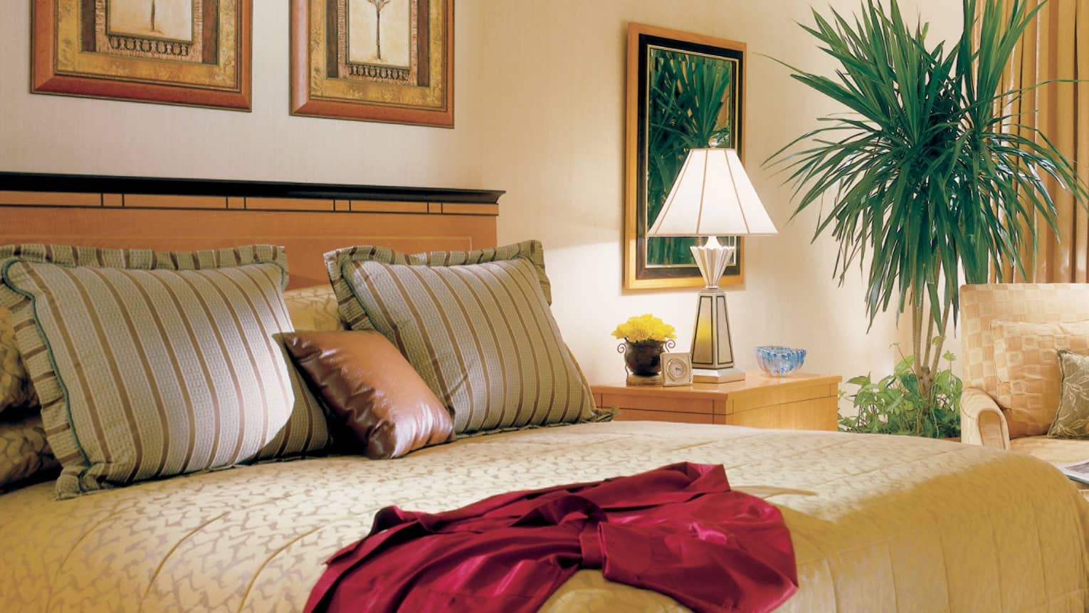 Nile Suite close-up of bed with colourful striped pillows, red silk robe draped on side, tropical indoor plants nearby